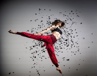 A woman wearing red trousers, mid leap, surrounded by swirling black confetti