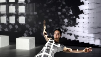 A dancer on their knees with black and white square projections all over the stage