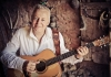 Tommy Emmanuel wears a white shirt and smiles whilst holding a guitar