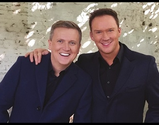 Aled Jones & Russell Watson wear blue suits and smile at the camera