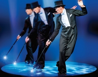 Three men in black top hats and tails dance with canes in a spotlight against a blue background