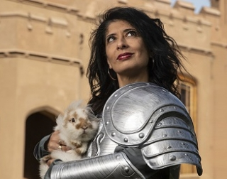 A woman in a suit of armor carries a bunny rabbit