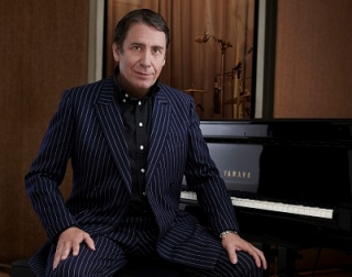 Band leader Jools Holland sits at a black Yamaha piano, wearing a dark blue pin-striped suit.
