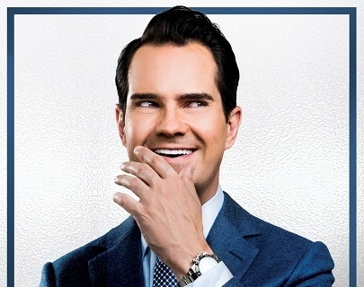 Jimmy Carr laughs into his hand whilst looking to the side, wearing a navy suit and a patterned tie.