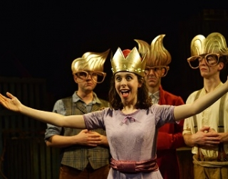 A princess in a pink dress and crown holds her arms wide, as men in large glasses and gold wigs look on.