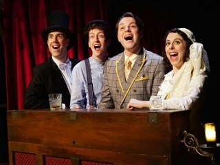 Four music hall performers stand behind an upright piano and sing