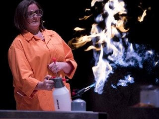 A woman in a lab coat and googles creates flames