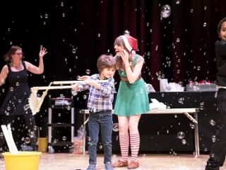 A woman dressed as an elf and a young boy are surrounded by bubbles on stage