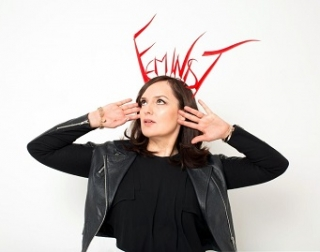 """Deborah Frances-White, a woman with brunette hair, frames her face with her hands, palms facing us. She wears a big head-dress which reads """"FEMINIST"""""""