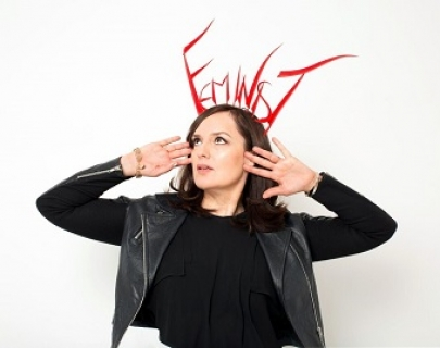"Deborah Frances-White, a woman with brunette hair, frames her face with her hands, palms facing us. She wears a big head-dress which reads ""FEMINIST"""