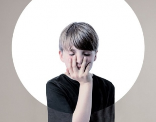 A young boy in a black shirt with his hand over his face