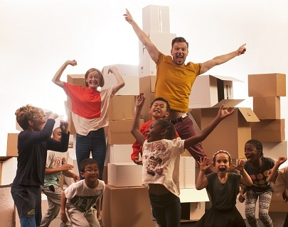 A man, woman and a group of children jump excitedly in the air in front of a pile of cardboard boxes.