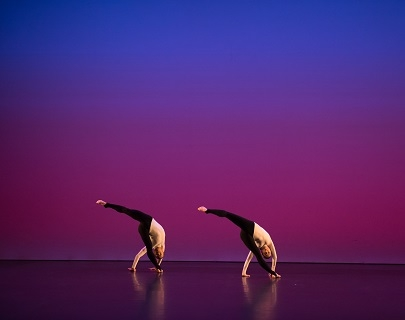 Two dancers on a purple and blue background