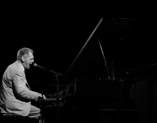 A man sings passionately into a mic on a piano. The photo is in black and white