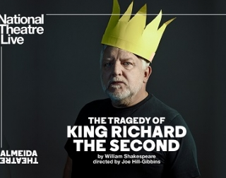 A man in a dark grey t-shirt with a large yellow paper crown on his head
