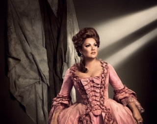 Adriana Lecouvreur, a beautiful brunette woman in a large pink ball gown