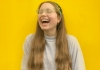 Performer Jessie Cave wears a grey jumper and laughs against a yellow background