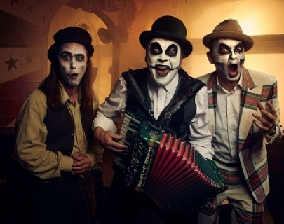 The Tiger Lillies: Men with white greasepaint and skeletal face paint, waistcoats and in instruments.