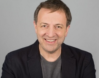 Author Misha Glenny wears a grey top and black jacket against a grey background