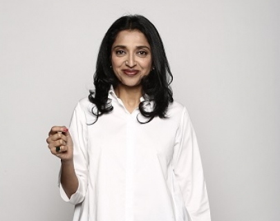 Comedian Sindu-Vee wearing a white shirt on a grey background
