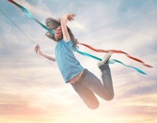 A girl flies joyously through the air, a sunset behind her and the strings of a kite trailing in the breeze behind her