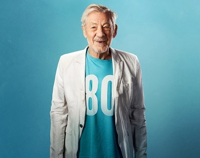 "Actor Ian McKellen smiles against a blue background, wearing a white jacket and a blue t shirt saying ""80""."
