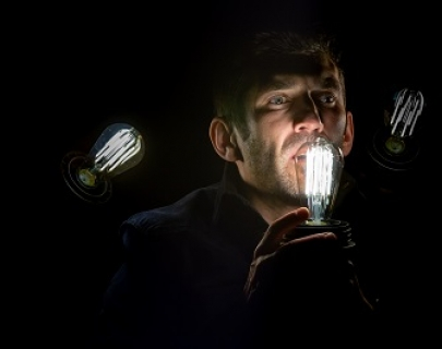 A man's face surrounded by glowing lightbulbs