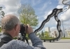 A man taking a photo of a statue on Warwick campus on his dslr camera