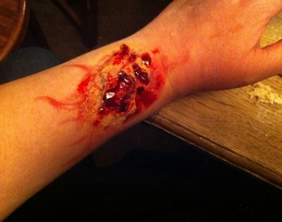 FX makeup has been to applied to an arm to make it look as if the person is injured, with their skin torn and blood in the wound