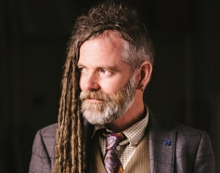 Duke Special, a man with a short beard and dreadlocks that fall on one side, wearing a suit and waistcoat