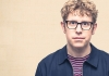 Comedian Josh Widdicombe stares at the camera, wearing a blue jacket and striped top.