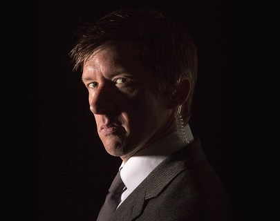 Comedian Jonathan Pie, wearing a suit and an earpiece, half in shadow and looking towards the camera