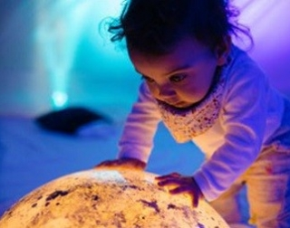 A baby places its hands on a gently glowing globe, watching the orange light with wonderment
