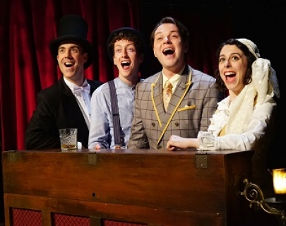 4 actors dressed in period vaudevillian clothes, in the act of singing energetically