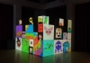A selection of blocks in a black space show a range of brightly coloured images made out of pixels