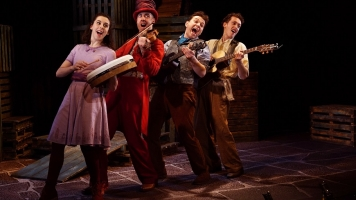 4 actors dressed in bright clothes, in the act of singing energetically with instruments