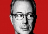 Ben Elton, photographed in black and white, against a bright red background