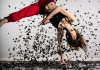 a woman in red trousers, balanced on one arm in a breakdance style, with black confetti sweeping around her