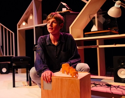 Performer Toby Thompson kneels on stage behind some wooden elephants on a box, in front of some wooden houses.
