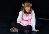 A female performer wearing a fluffy hat, white waterproof jacket and walking boots sits on a black stage
