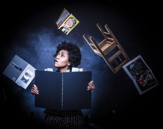 A woman holding a large book looks up a flying objects, such as a chair and other books