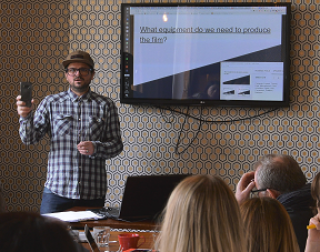 A man in a checked shirt and a hat stands in front of a powerpoint about film equipment