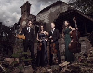 2 men and 2 women in formal dress stand with string instruments from violins to cellos, stand in front of an abandoned building