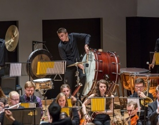 An orchestra, comprised of percussion and wind instruments