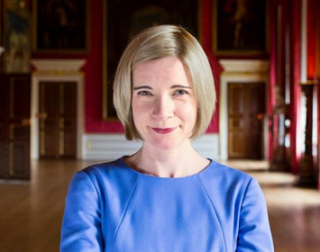 Lucy Worsley,a woman with short blonde hair and wearing a blue dress, stood in a historic stately home