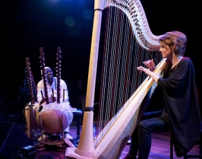 A woman plays the harp, a man smiles at her from behind an array of instruments on the stage