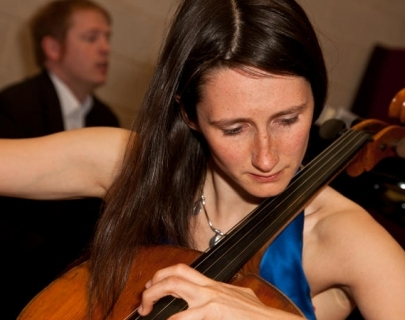 A female musician in a blue dress with long hair playing the cello