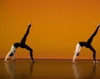 Two dancers perform on a burnt orange background
