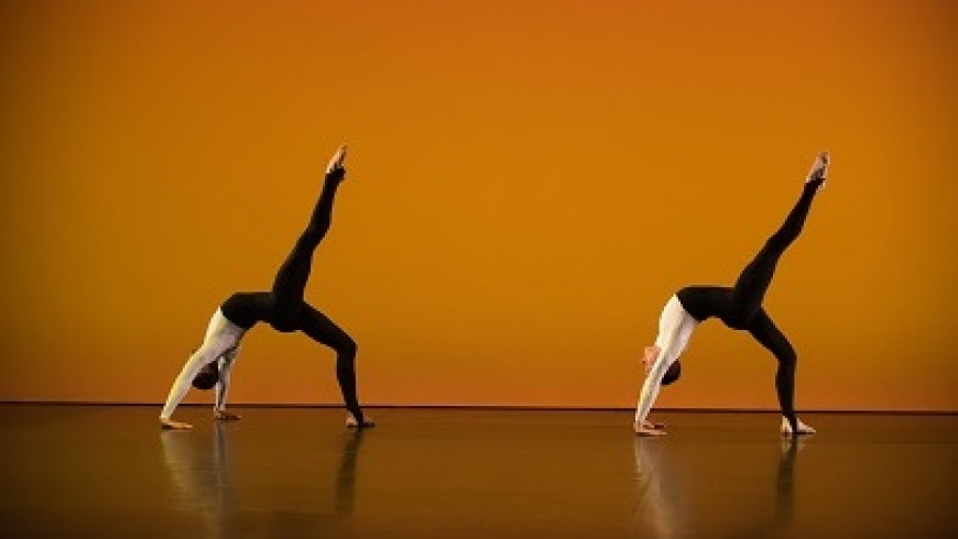 Two dancers perform on a burnt orange background