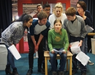 A group of children huddle around each other performing holding scripts.